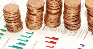 Business concept - Stacks of coins on various bar charts