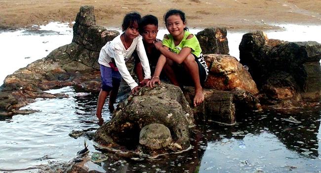 Tiga pengunjung berfose di batu Malin Kundang, yang terlihat tengah bersujud.