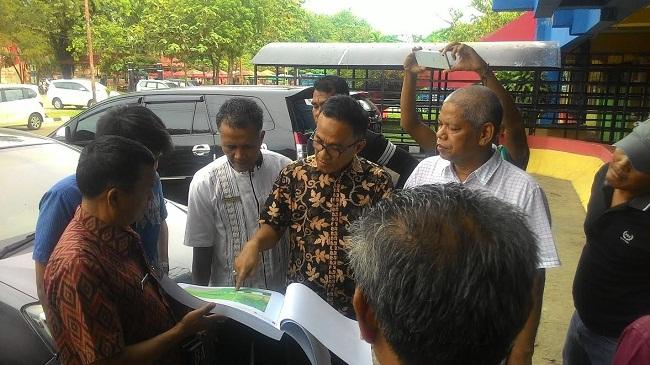 Kepala Dinas Pekerjaan Umum Kota Padang, Fitriarman Noer memperlihatkan gambar perencanaan pembangunan kawasan olahraga di GOR H. Agus Salim kepada Dirut PT Kunango Jantan Group H. Asril saat peninjauan komplek itu, Jumat (3/2). (dede amri)