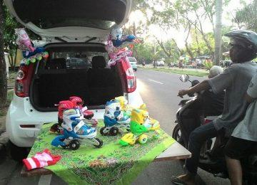 Seorang pria menawar sepatu roda, yang dijajakan Miko di kawasan Padang Baru. (yuke)