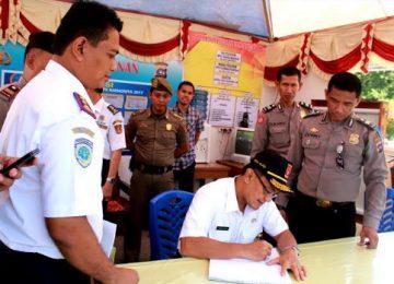 Bupati Agam, Indra Catri disaksikan Kepala Dinas Perhubungan, Budi Perwira Negara, mengisi buku tamu pak Pos Pengamanan (Pospam) Lebaran 2017.(maswir)