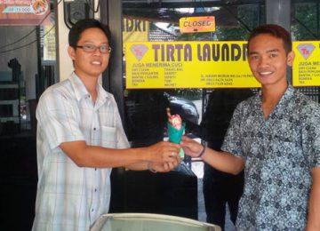 Owner Es Krim Alah Tibo, Yudi Pratama Halim tengah memberikan es krim kepada konsumen yang membeli salah satu varian es krim tersebut, Senin (12/6). (deri oktazulmi)