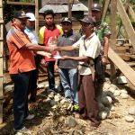 Camat Pauh Duo Zam Zami disaksikan Babinsa Tasrif dan Wali Nagari di Pauh Duo tengah menyerahkan bantuan Wakil Bupati H. Abdul Rahman pada keluarga Alimar di Sungai Duo. (Afrizal Amir)