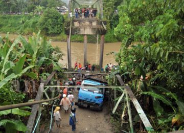 Sejumlah warga berada di dekat mobil truk yang jatuh akibat jembatan yang ambruk, di Nagari Sikabu, Kec.Lubuk Alung, Kab.Padangpariaman, Sumatera Barat, Senin (14/8). (antara)