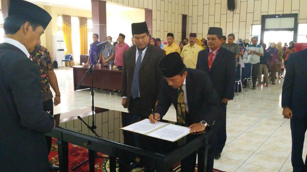 Sekretaris Dinas Nakertrans, Ahmad Jaya tengah membubuhi tanda tangan usai pengucapan sumpah dan pelantikan, disaksikan Bupati H. Muzni Zakaria di aula Sarantau Sasurmabi, Kamis, (7/9). (*)